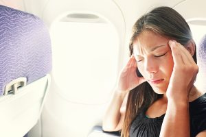 Fear of flying woman in plane airsick with stress headache and m
